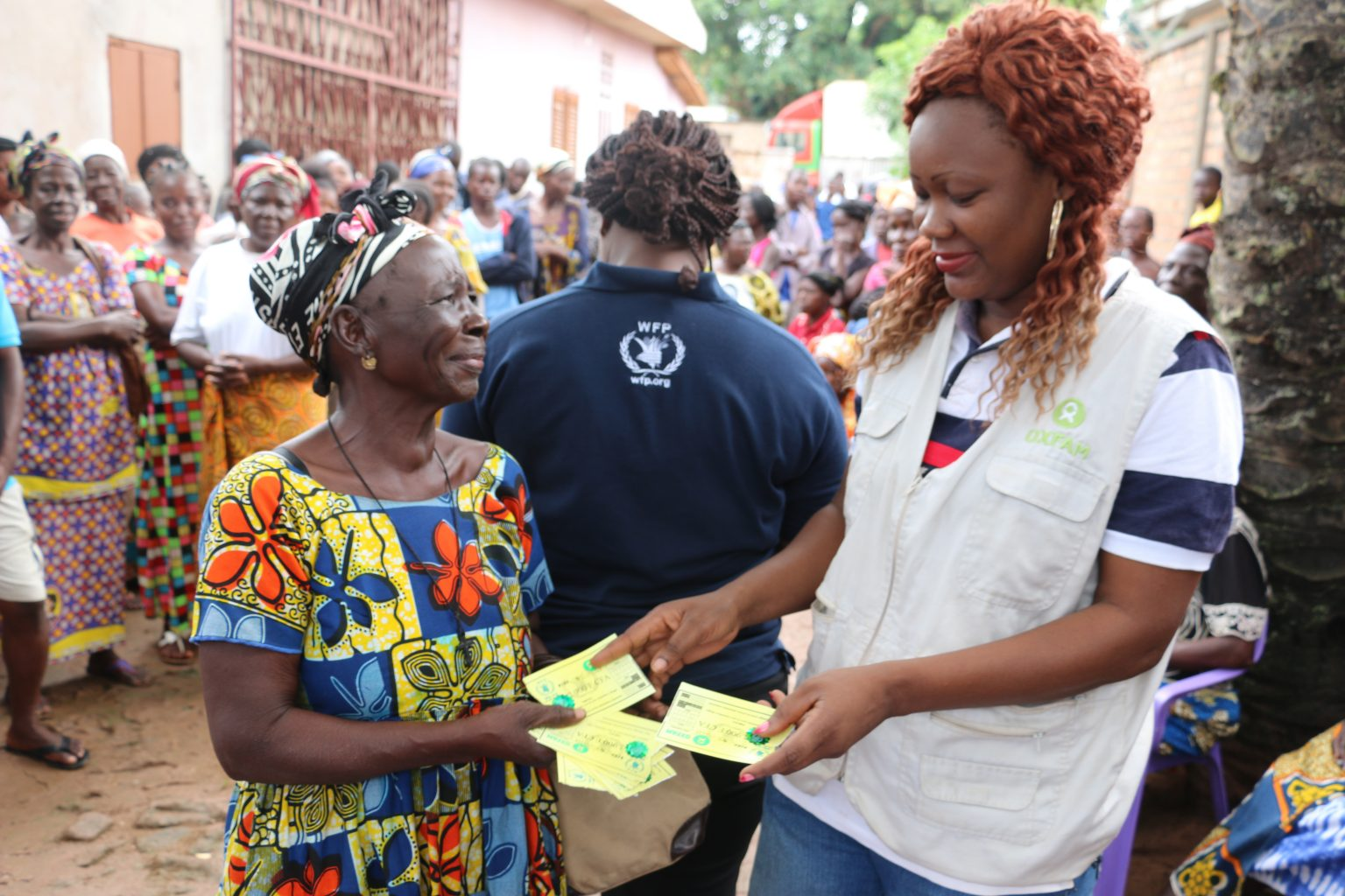 An elderly woman receives food vouchers from a WFP aid worker