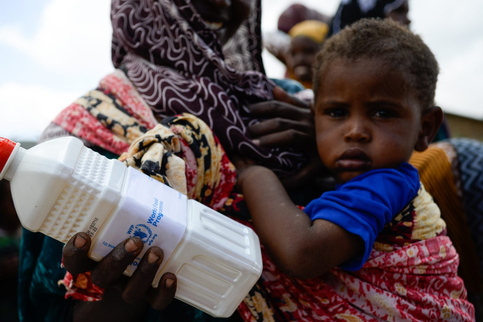A young child in his mother's arms, as she also holds a bottle of WFP-issued vegetable oil