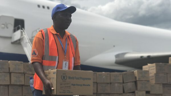 A WFP aid worker carries a box of High-Energy Biscuits with a plane in the backdrop