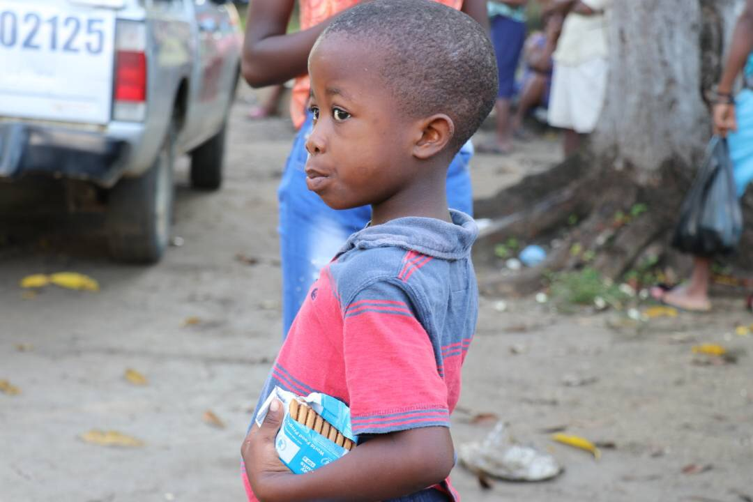 A young boy holds an open package of High-Energy Biscuits while looking off camera