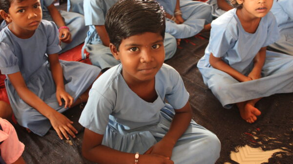Rani sits on the floor of her classroom, surrounded by classmates, all wearing blue dresses for uniforms