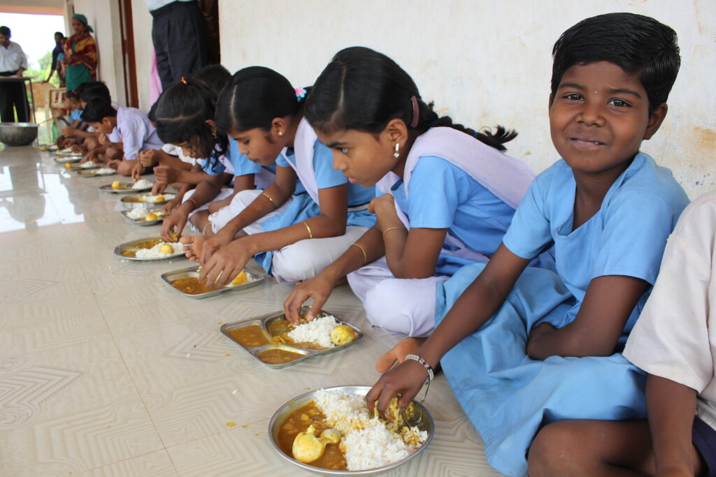 Young girls in blue school uniforms sit on the floor to eat a meal.