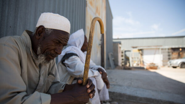 An elderly man in a skullcap and beard sits with his cane outside a warehouse, looking down