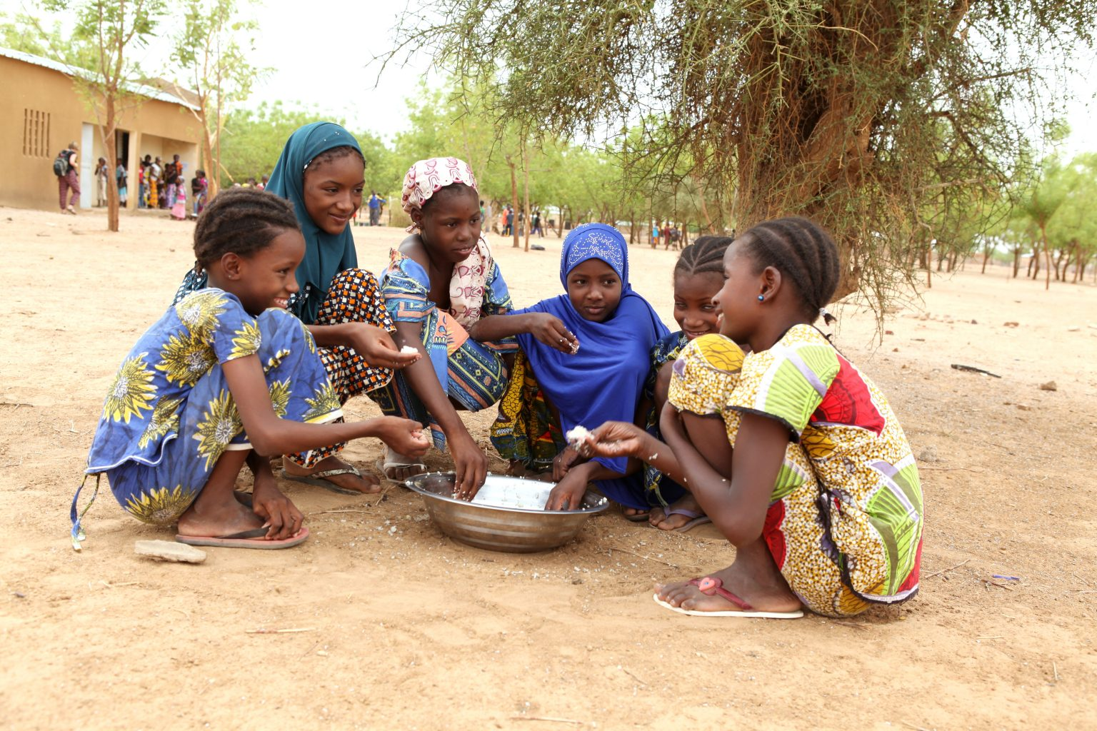A group of girls sits on the ground, eating and chatting over a shared bowl of food