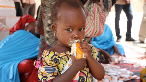 A young girl eats from a Plumpy'Sup packet with food all over her mouth