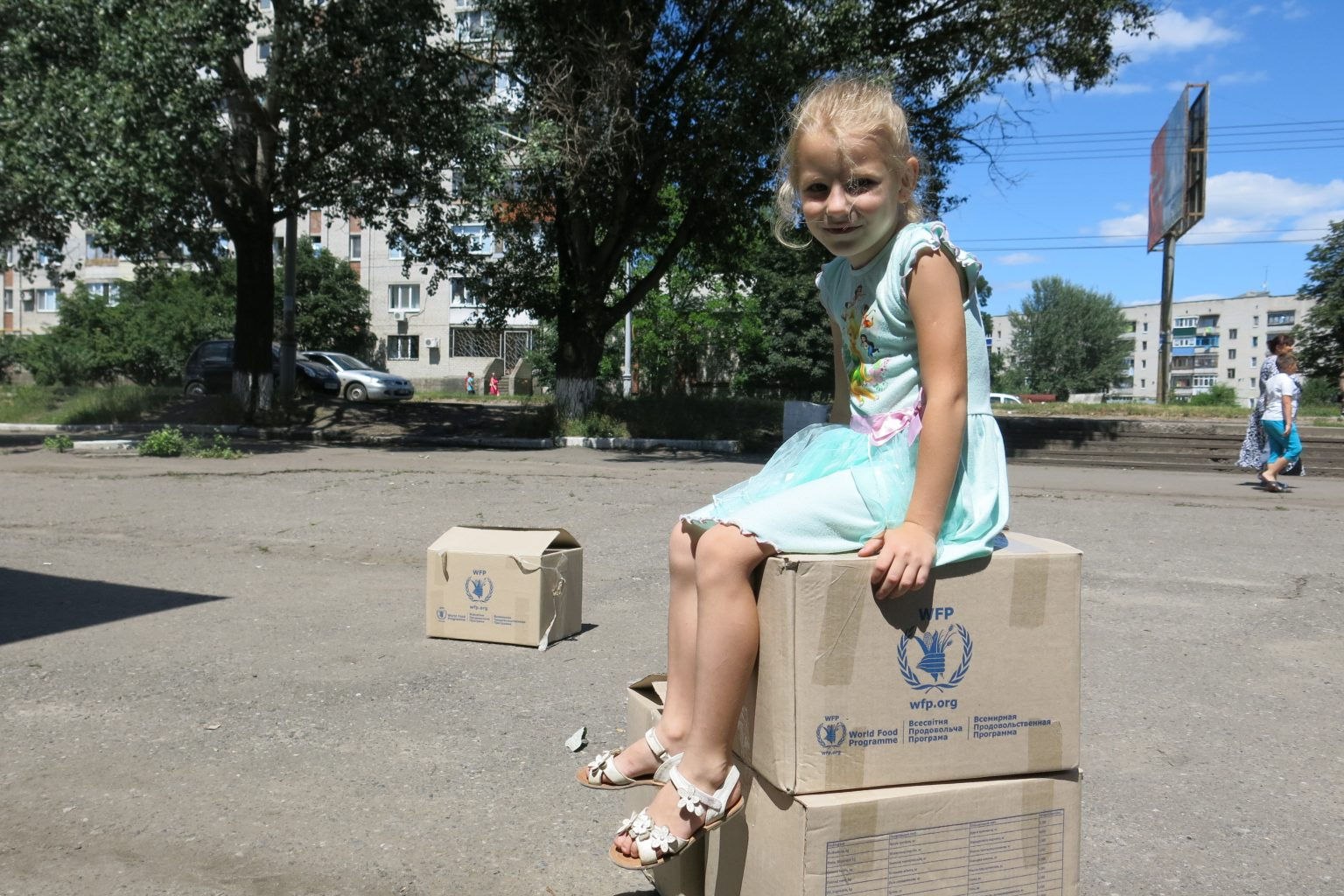 A young girl sits on WFP food boxes given to her family