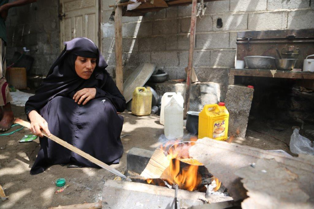 Aisha in her black hijab kneels on the ground to light up a makeshift stove using cardboard