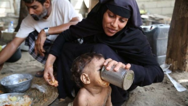 Aisha in her black hijab feeds Wafaa water out of a tin can, her husband Fadl sits behind them