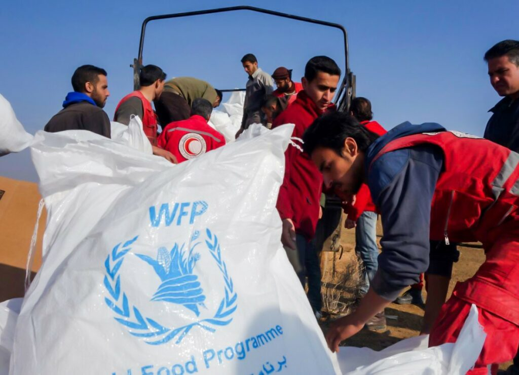 SARC volunteers in red vests collect WFP bags and pallets to load onto trucks