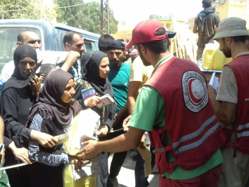 A SARC volunteer in a red vest hands out food assistance to men and women