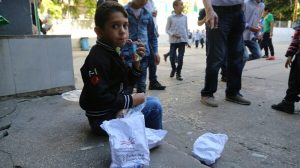 A young boy sits on the curb with his school meal bag beside him and drinks from a juice box