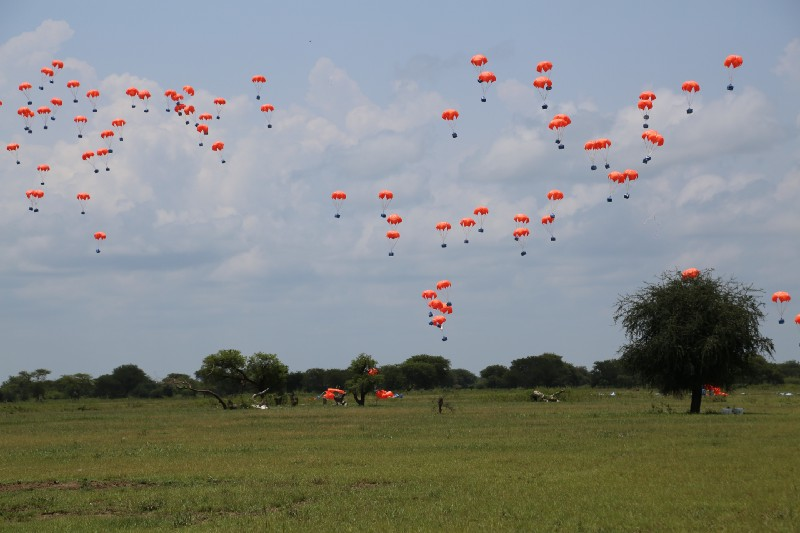 Parachutes of vegetable oil fall to the ground from an airdrop of 1,000 feet.