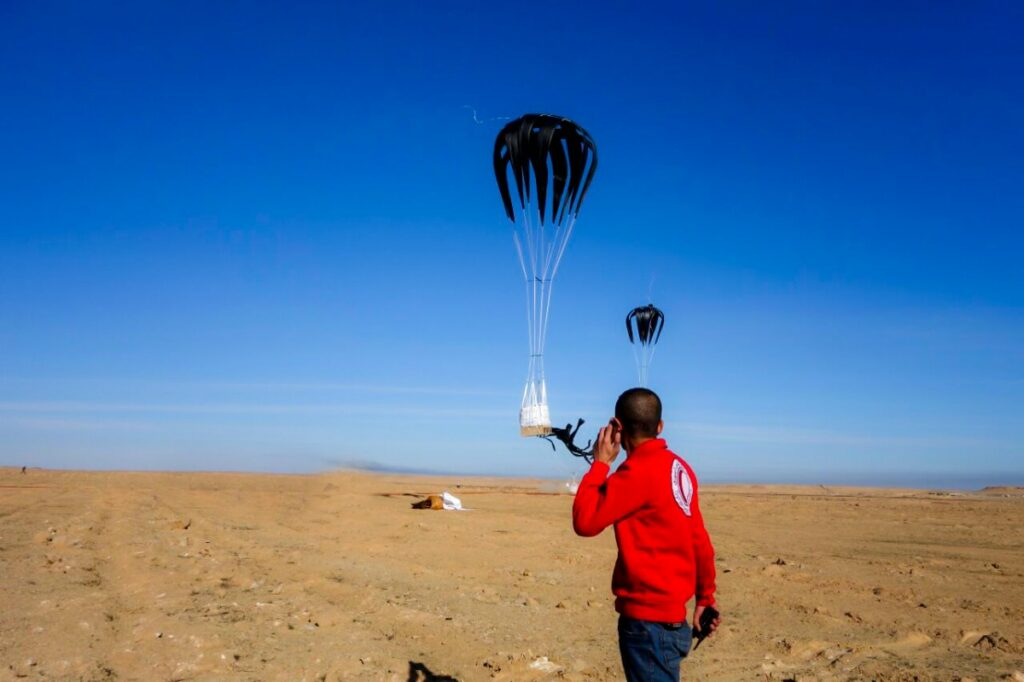 A pallet with parachute drops to the ground, a SARC officer on the phone looks in the distance