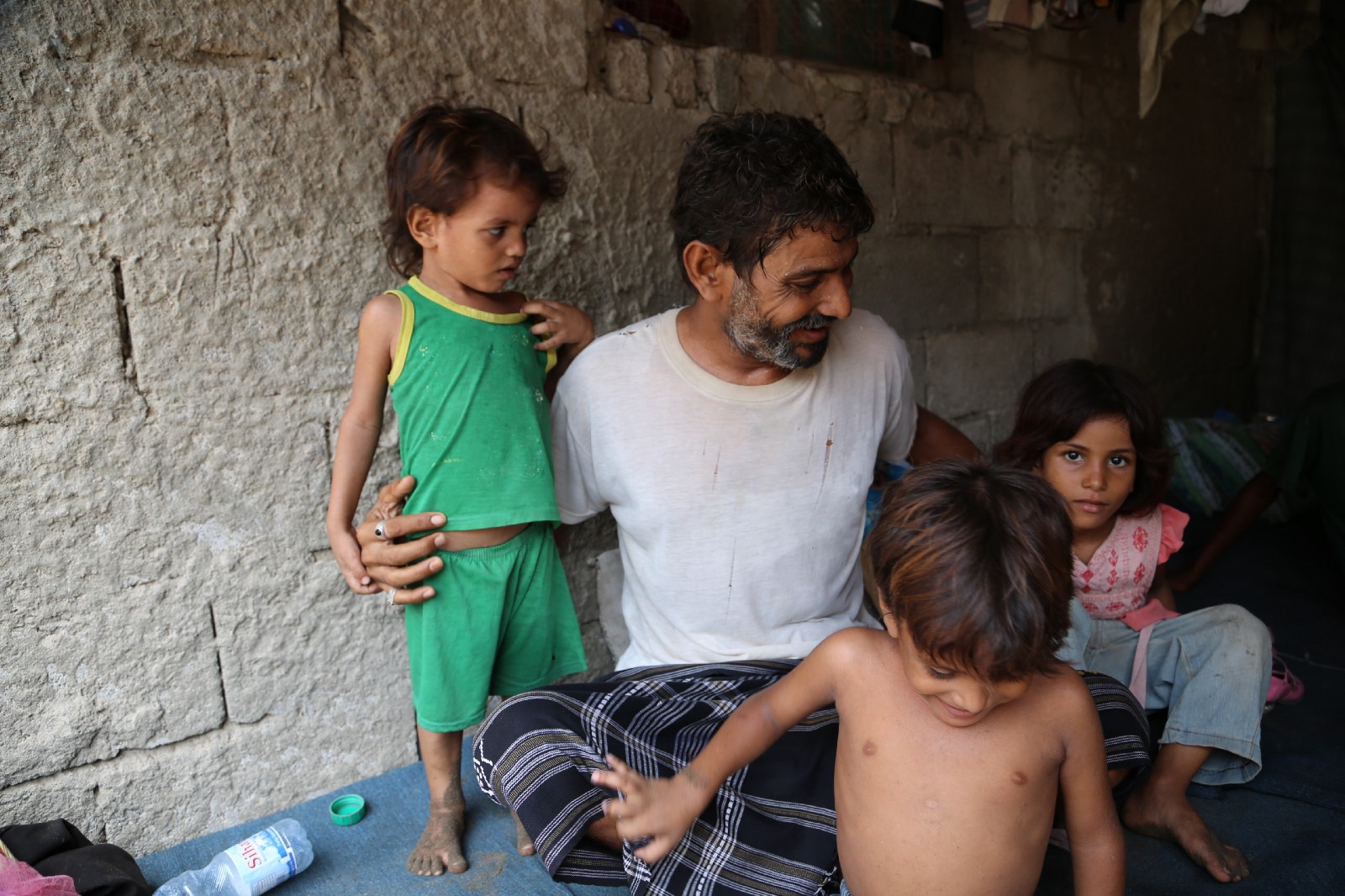 Fadl sits beside three of his children, they all hold onto him