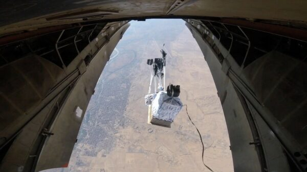 Pallets of food assistance are released out of the back of a cargo plane, camera is looking down over the landscape as they are released