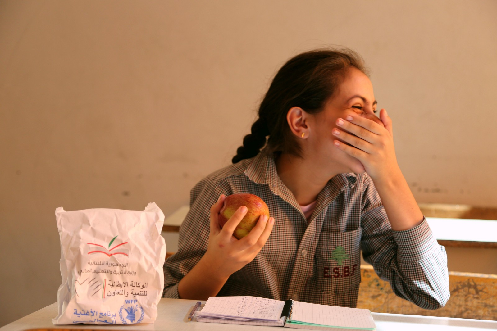 Karla takes an apple from her school meal bag and covers her mouth as she laughs
