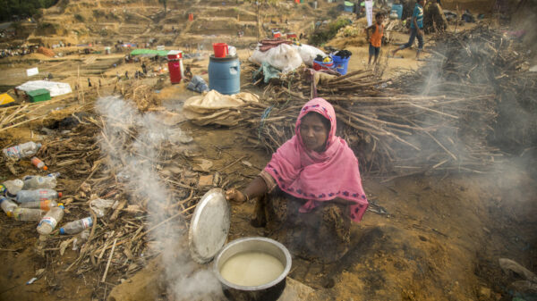 Munzila wears a pink scarf over her head and lifts the lid of a pot of rice, her belongings surround her