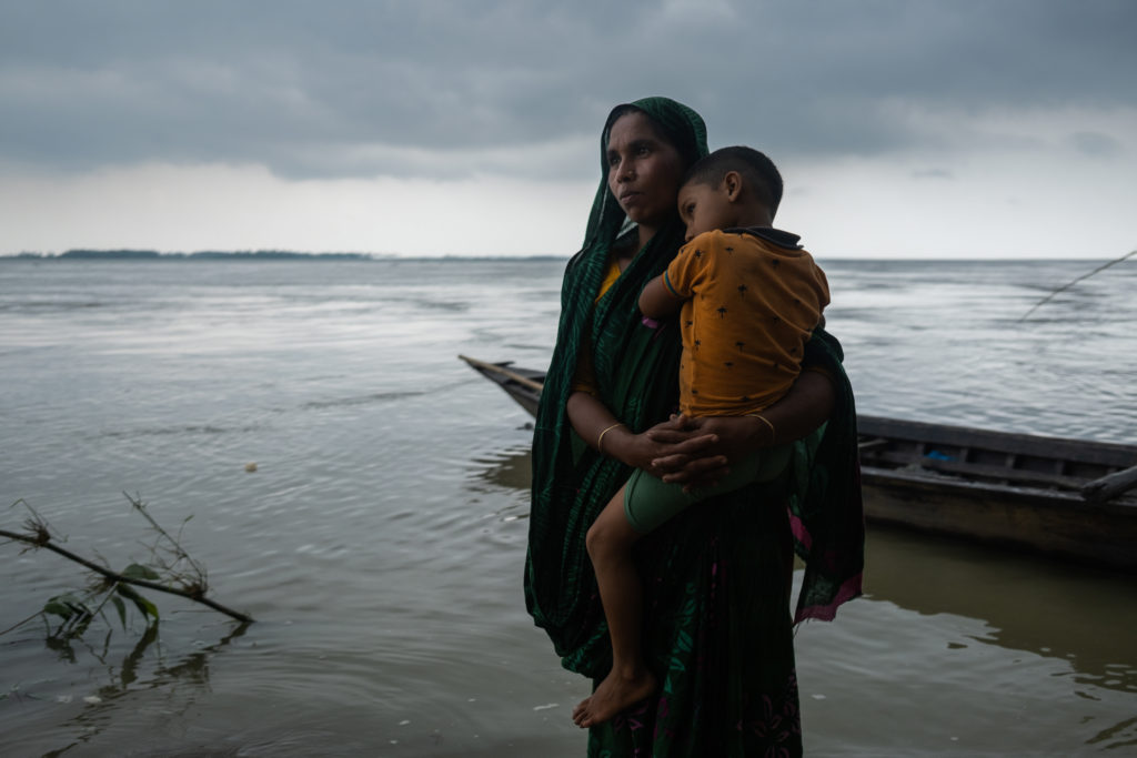 A woman stands in knee-deep water holding her child