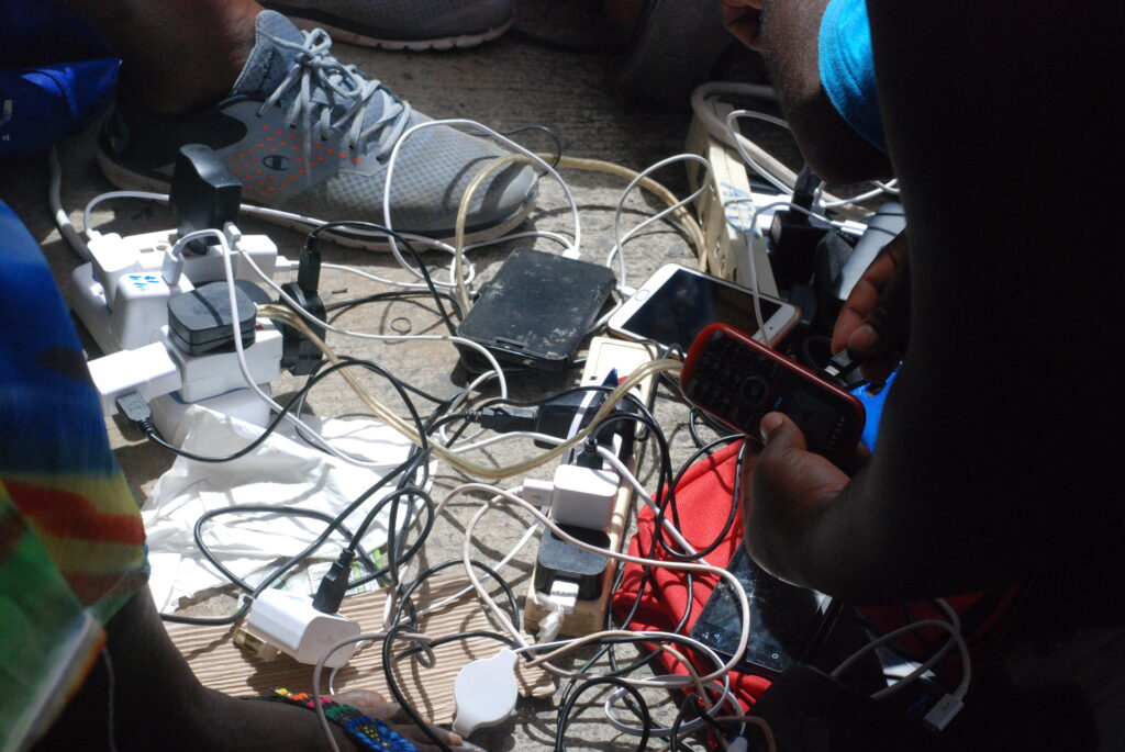 Cell phones being charged in a tangle of wires with the help of simple generators
