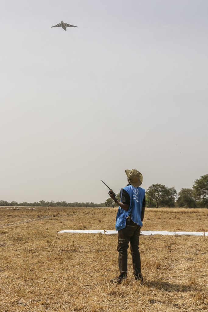 WFP Drop Zone Coordinator, Hezron Kabburu, observes the approach of an Ilyushin-76, which is about to drop bags of cereal in Thaker, Mayendit County of South Sudan.