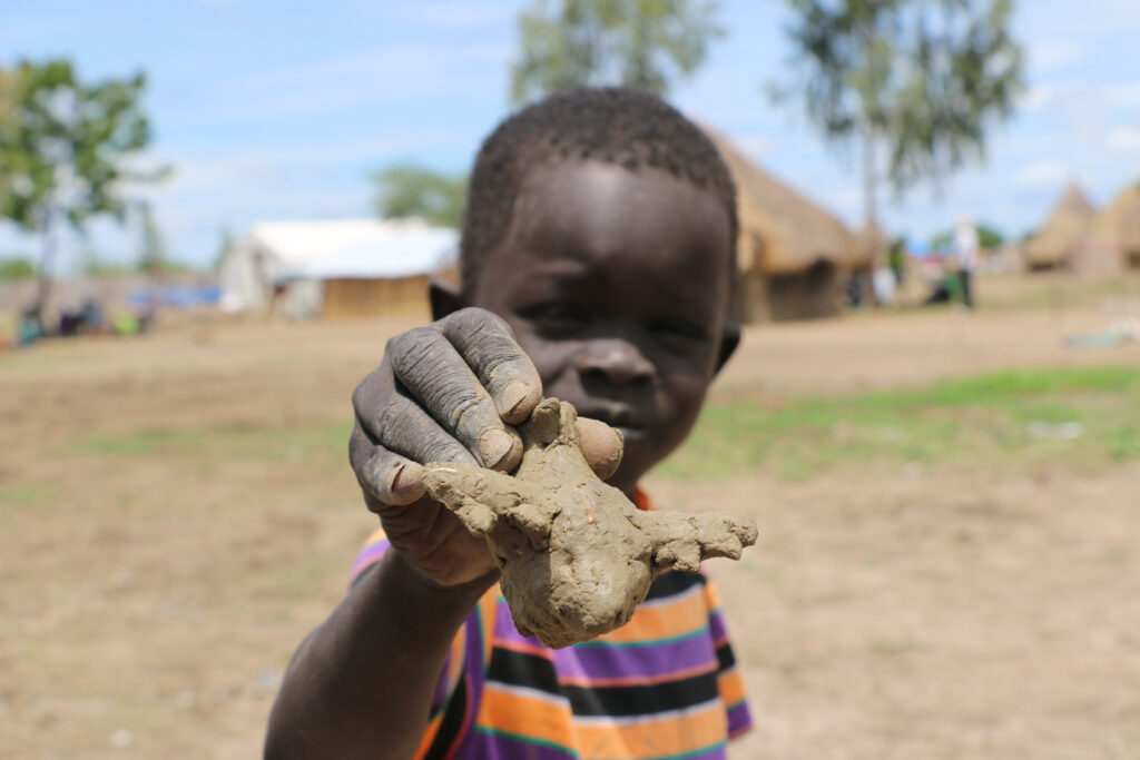 7-year-old Peter Mabor holds up a model airplane that he has made out of mud