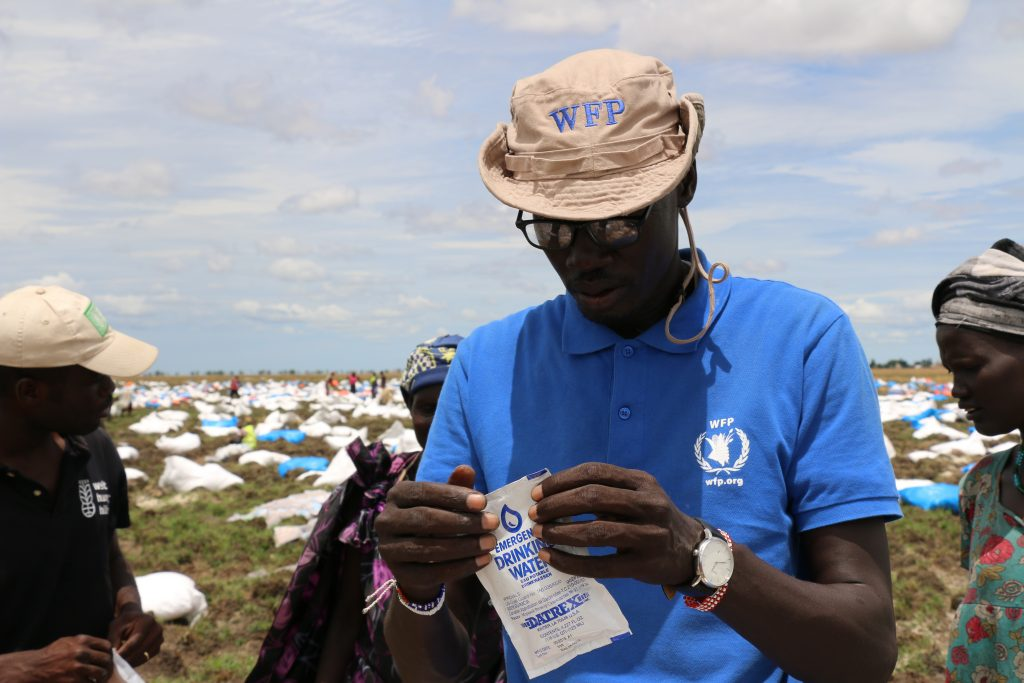 WFP drop zone coordinator, Kang Koriyom, opens a packet of drinking water after an airdrop in Ganyiel, Unity State.