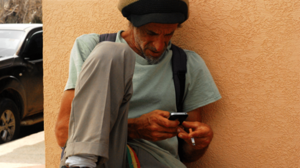Shergill sits on the ground and looks down at his cell phone, holds his cigarette in one hand