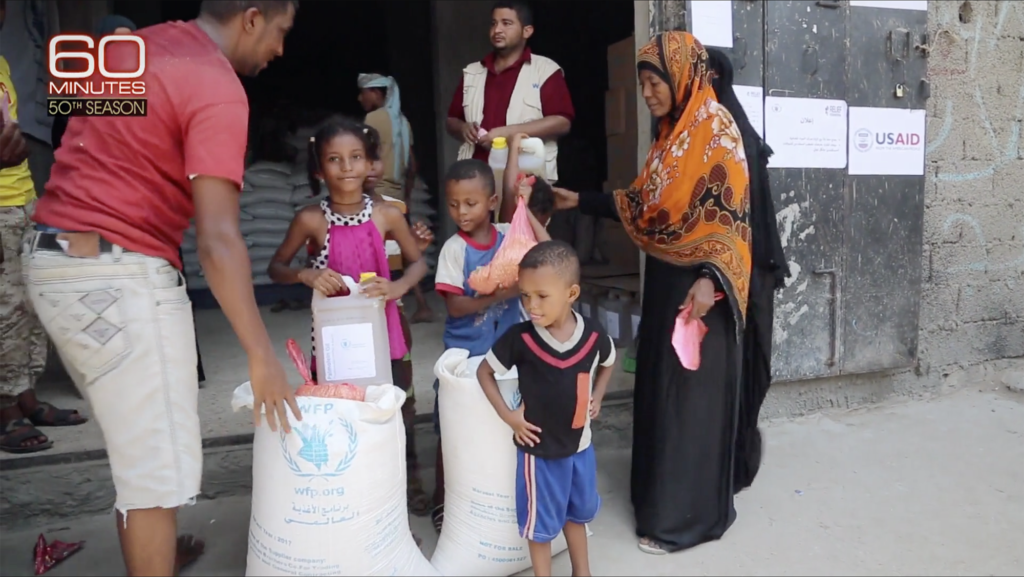 A family gathers around their food rations from WFP in large white bags and cartons of oil