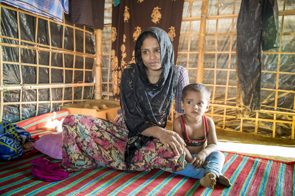 Hamida and her son sit on the floor of a tent
