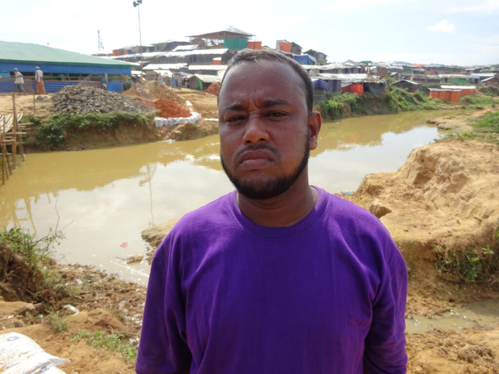 Sham Allam looks at the camera, wearing a purple shirt