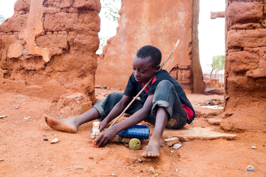 A boy sits on the ground with a racing car he made out of sticks, string and an empty water bottle.
