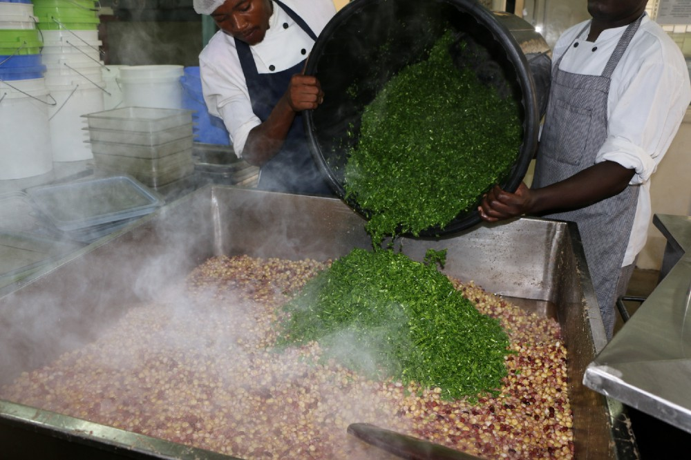 Cooks at the Little Bells Primary School in Kenya prepare a nourishing meal for the students using locally grown green beans that had been rejected for export for cosmetic reasons.