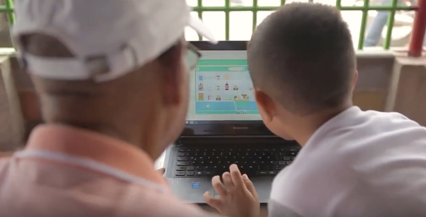 "A grandfather and grandson in Colombia explore WFP's a nutrition education app called ""Nutrifami,"" which is available for free on smartphones and in the country's Internet cafes."