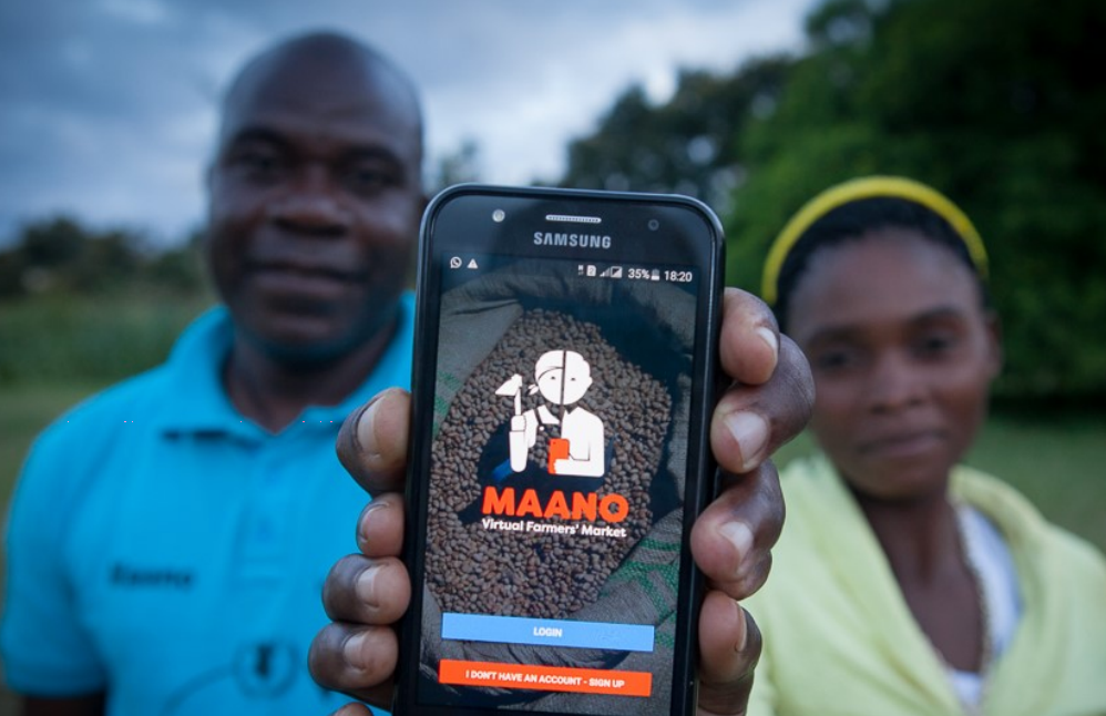 "A couple in Zambia hold up a smartphone showing the interface for a free new app called ""Manoo."" Developed by WFP, this virtual farmers' market connects buyers and sellers in the country's agricultural sector, making it easier for farmers in remote areas to access markets and information like food prices."