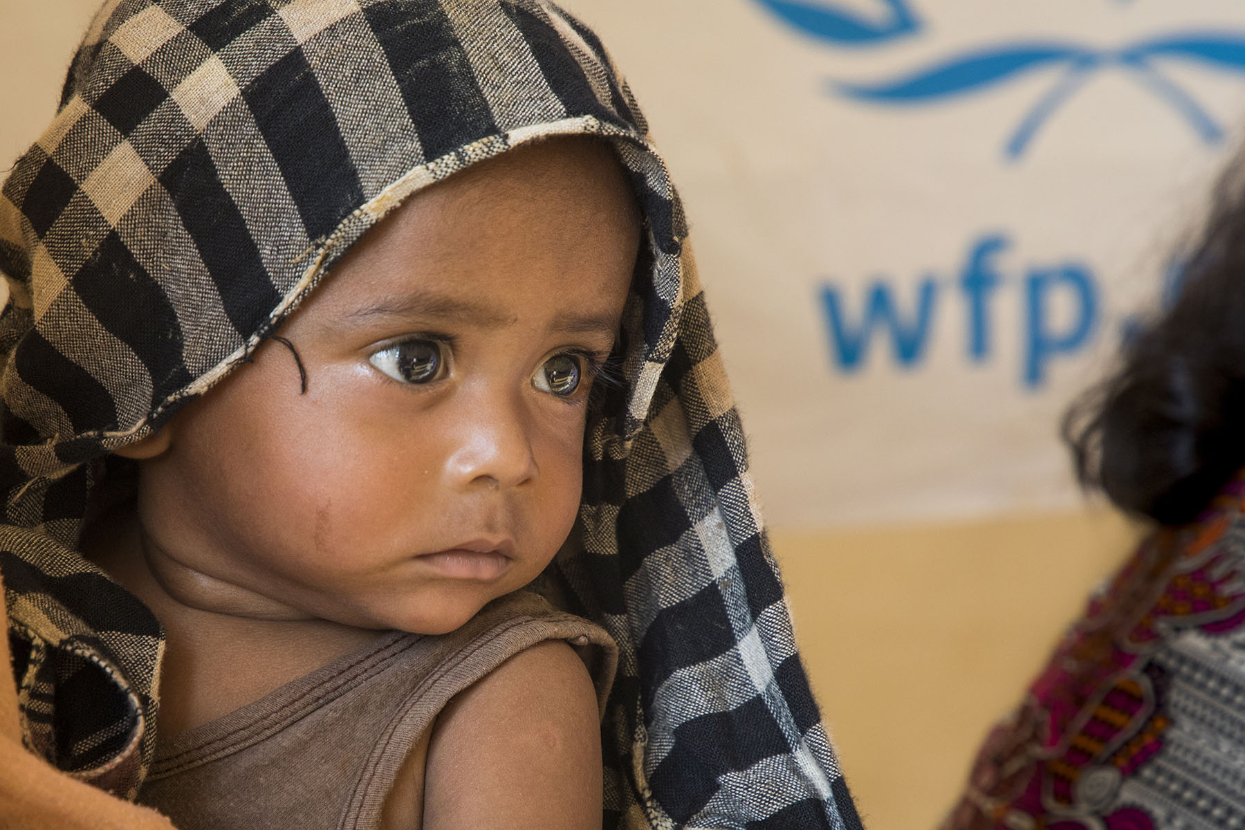 A young child waits at a food distribution site in the Kutupalong camp in Cox's Bazar, Bangladesh.