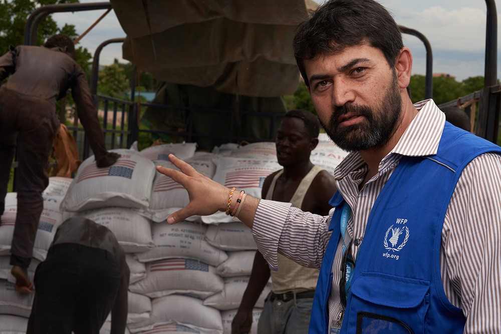 Adham Effendi, WFP's head of logistics in South Sudan, oversees food being transferred from trucks arriving in Juba from outside South Sudan to trucks transporting the food to various locations inside the country.