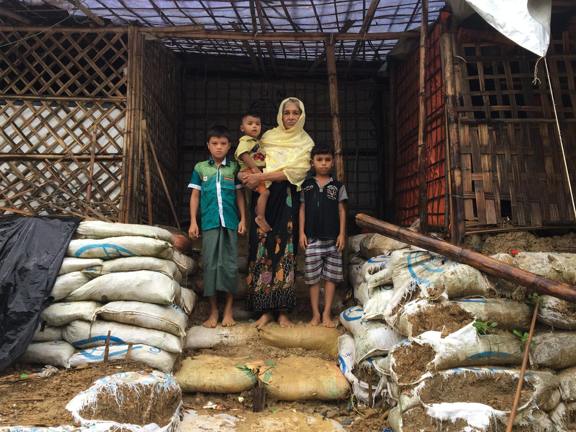 a woman stands outside her home with her family