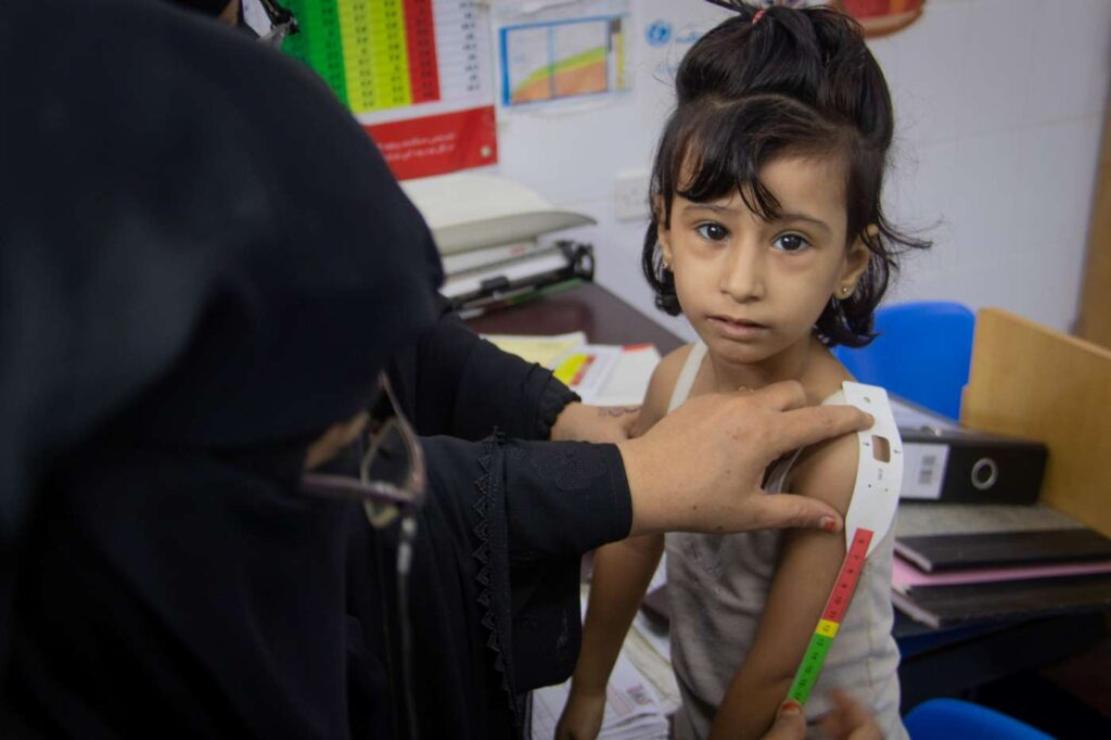 a young girl has her arm measured at a health center in yemen