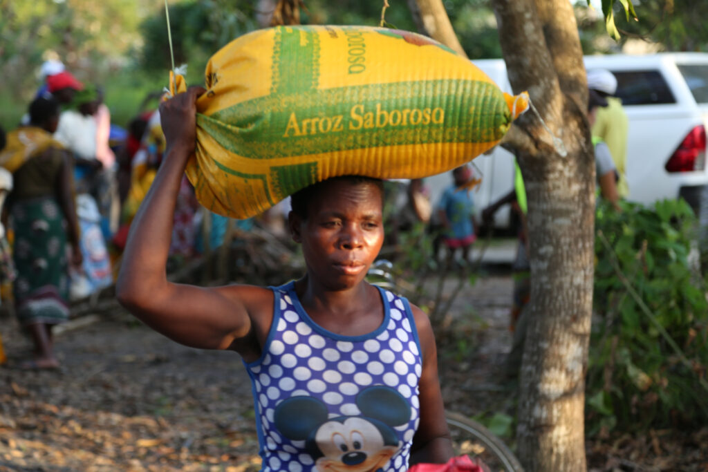 A woman carries a sack of food on her head.
