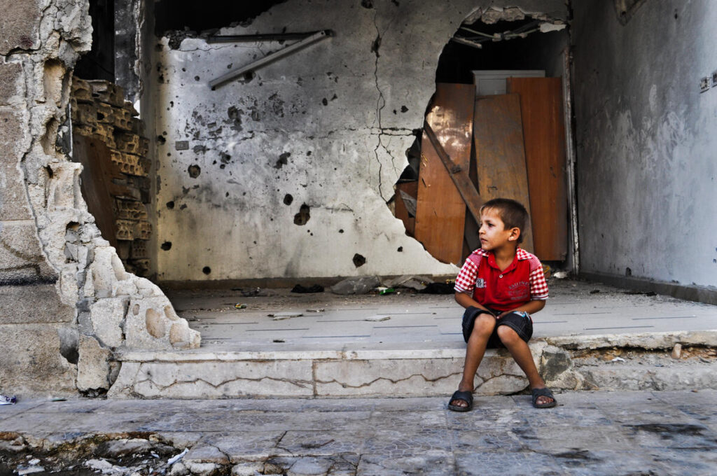 A young boy sits outside a destroyed building.