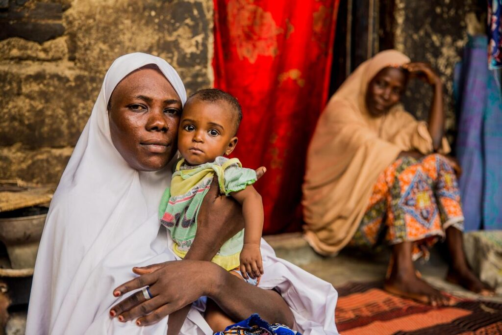 A mother sits, holding her child, with another woman nearby.