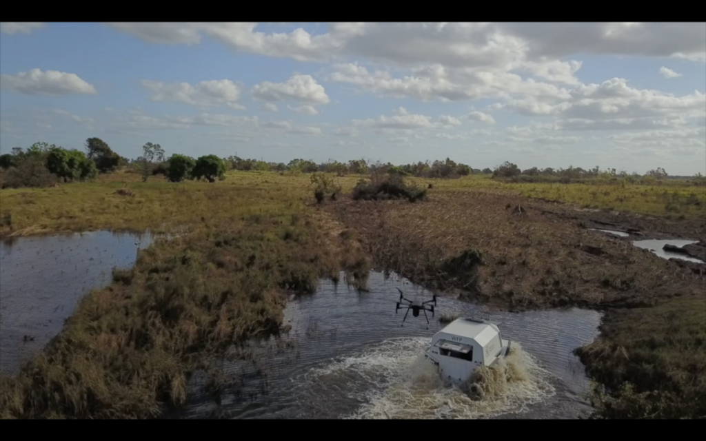 Drone footage of a SHERP vehicle driving through a river