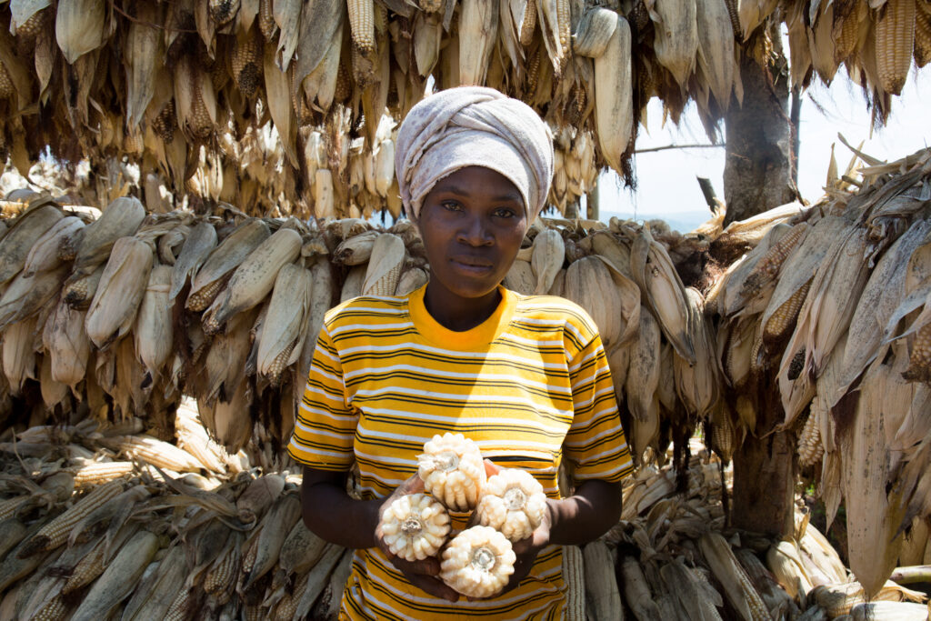 28-year-old Fideline Ayinkamiye shows the corn she'll sell via the Farm to Market Alliance.