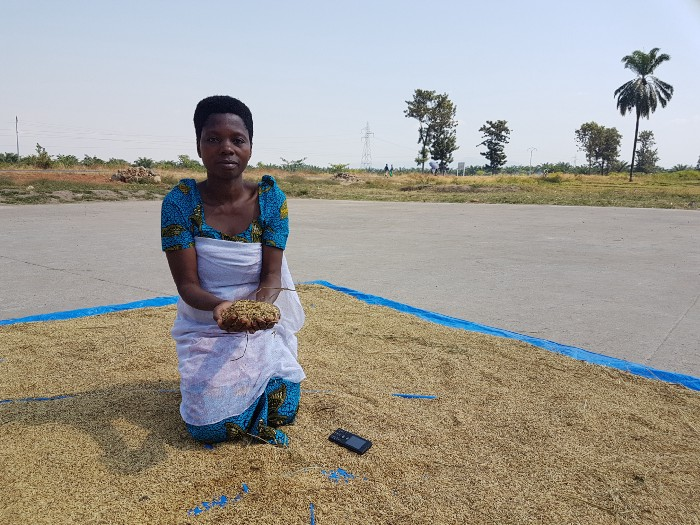 A woman in Burundi holds dried rice