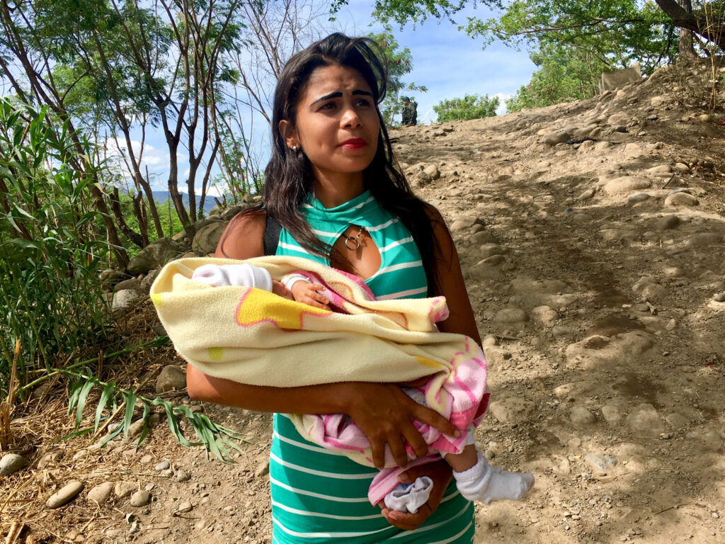 A mother carries her baby from Venezuela to Colombia to get medicine