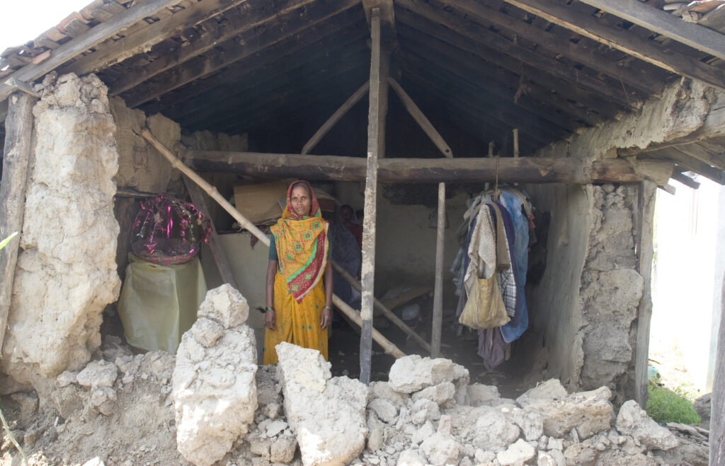 Gyanu Kori stands inside the remains of her family's home in Nepal