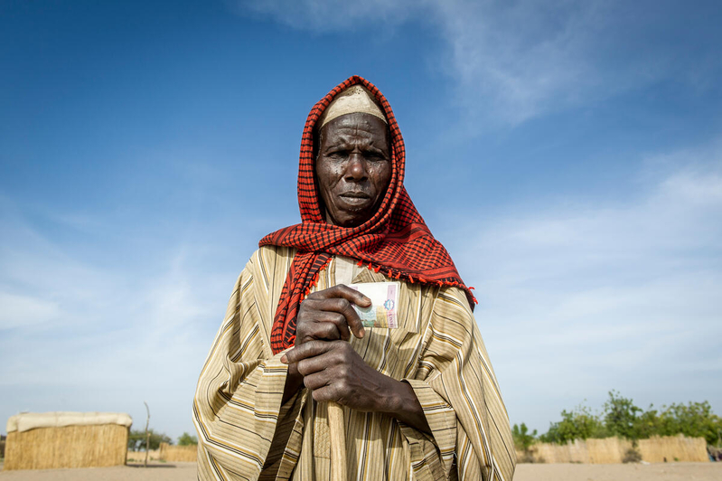 a woman in red headscarf holds cash from WFP