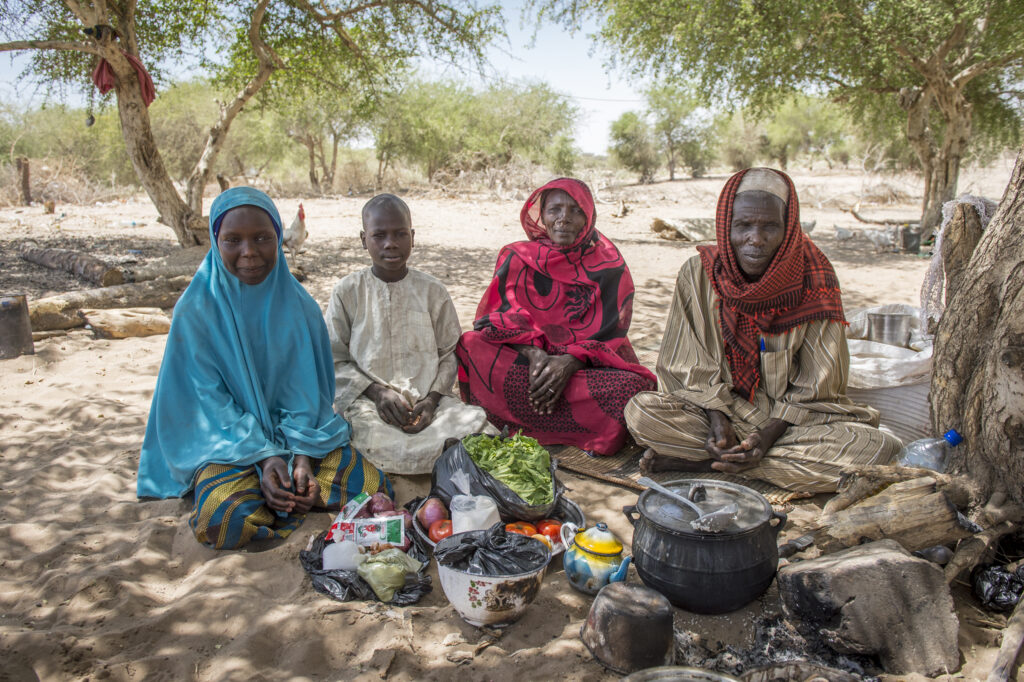 A family sits under a tree in Chad, Africa