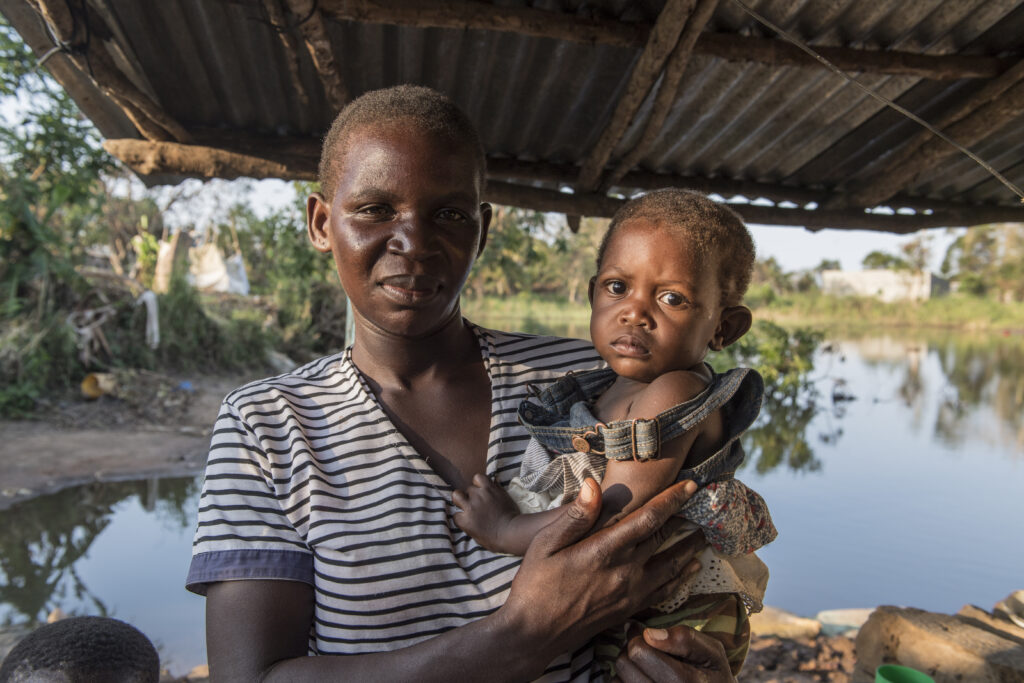 A mother and her baby stand in front of floodwaters in Mozambique
