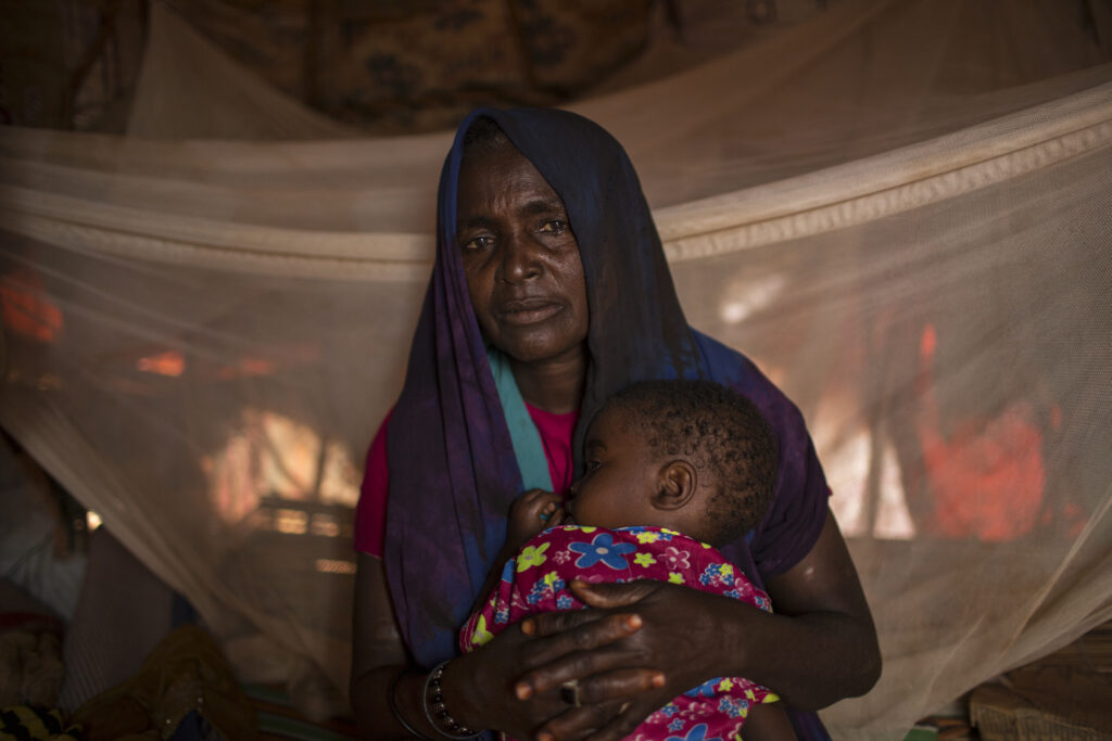 A woman comforts her granddaughter at her home in a camp for IDPs